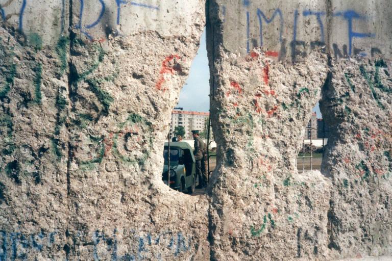 Um dos buracos abertos no Muro de Berlim em 1990, deixando à vista guardas de fronteira sem ter o que fazer