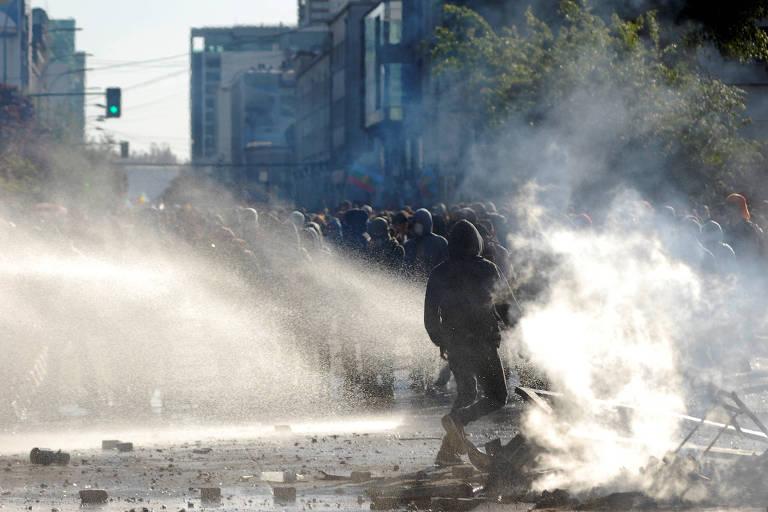Manifestante atravessa nuvem de gás lacrimogêneo