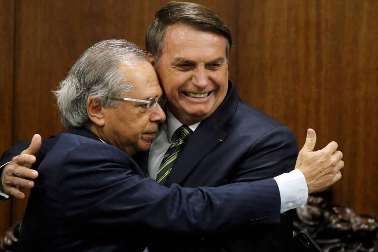 Paulo Guedes e Jair Bolsonaro se abraçam durante entrega de pacote legislativo ao Congresso