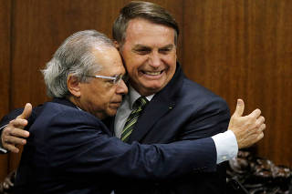 FILE PHOTO: Brazil's President Jair Bolsonaro greets Brazil's Economy Minister Paulo Guedes during a meeting to deliver the economic reform package at the National Congress in Brasilia