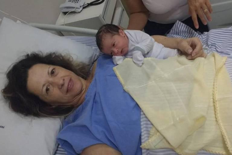 Em um leito hospitalar, Ana Maria está deitada, com roupas azuis, acolhendo seu bebê Ian, recém-nascido
