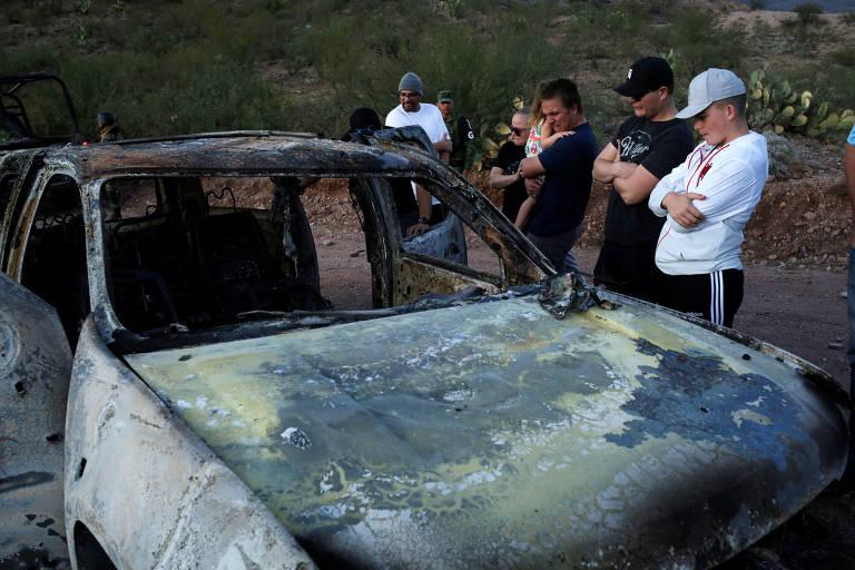 Parentes observam carro incendiado por criminosos em estrada no México