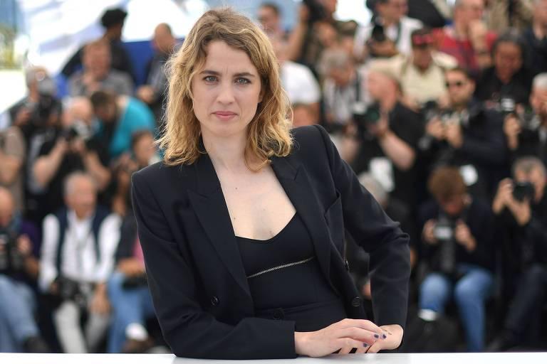mulher loira vestindo roupa preta posa para a camera
