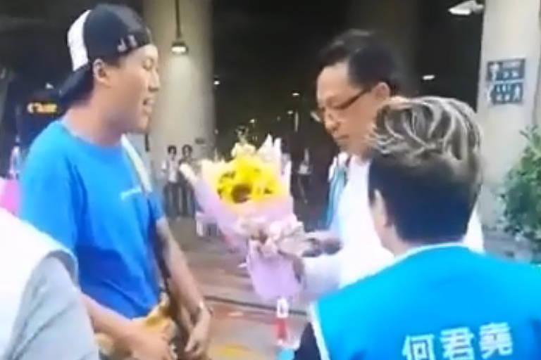 Homem entrega flores ao deputado Junius Ho logo antes de esfaqueá-lo, em Hong Kong