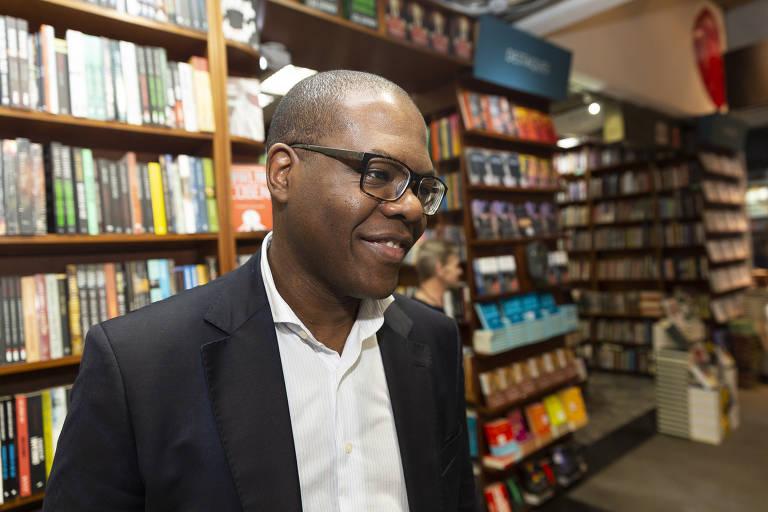 homem negro e de óculos diante de estantes de livros
