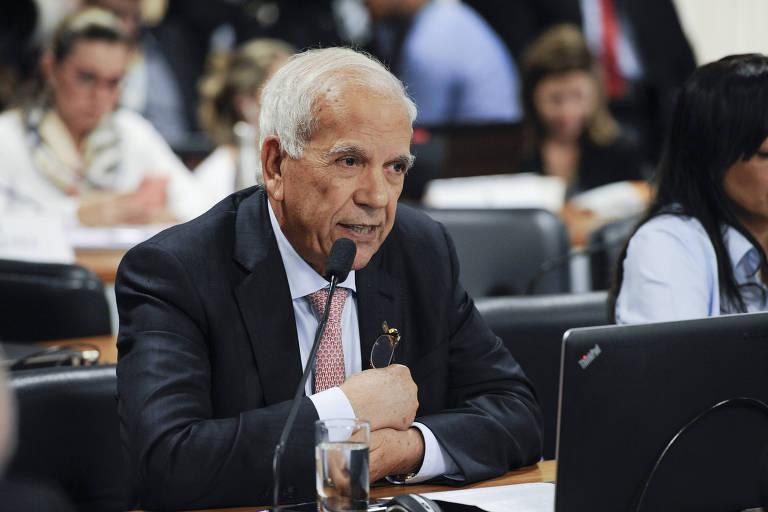 O senador Oriovisto Guimarães aparece sentado em uma mesa, com braços cruzados, falando em um microfone