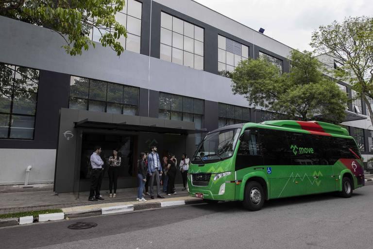 Funcionários do Bradesco esperam em frente a um ponto de ônibus em frente a um prédio cinza. Um ônibus verde está parado em frente, aguardando o embarque dos passageiros.