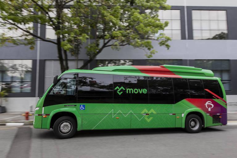 Um ônibus verde, com o logo do sistema de transporte interno Move na janela e com uma listra vermelha na parte de trás, com o logo do Bradesco, é visto andando pelas ruas dentro da sede do banco. Ele está passando na frente de um prédio cinza e de uma árvore.
