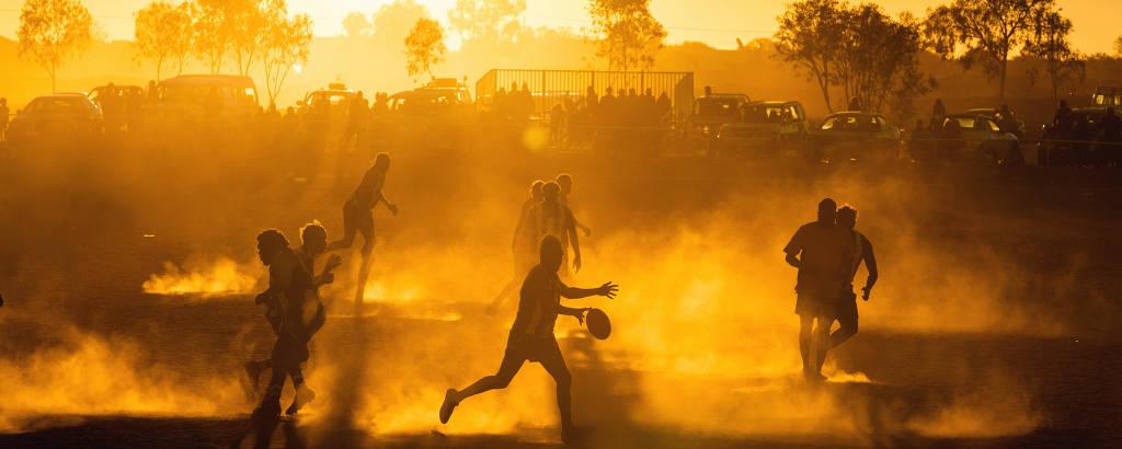 Jogadores de futebol do mato jogam sob o sol do deserto australiano
