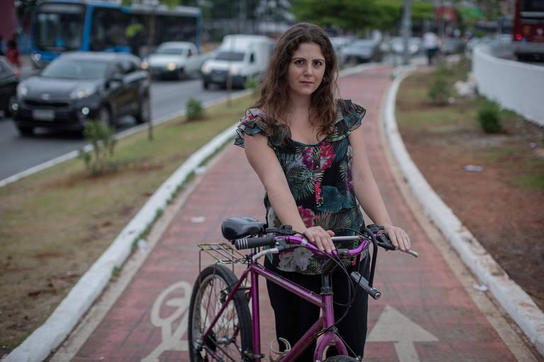 Imagem mostra mulher segurando bicicleta sobre ciclovia