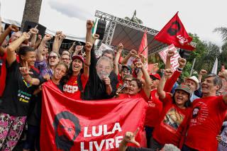 Supporters of Brazil's former President Luiz Inacio Lula da Silva gesture outside the Federal Police headquarters where Lula is serving a prison sentence, in Curitiba