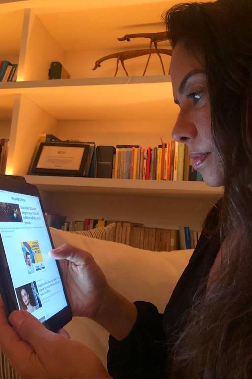 Retrato de mulher de perfil segurando um tablet onde está exibido o site da Folha de S. Paulo