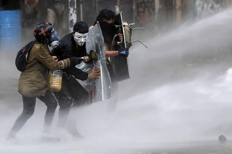 Manifestantes se protegem com escudos de jato d'água jogado pela polícia