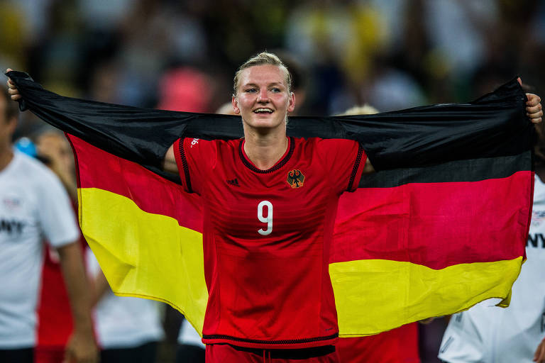 jogadora alemã comemora estendendo a bandeira amarela, vermelha e preta do país.