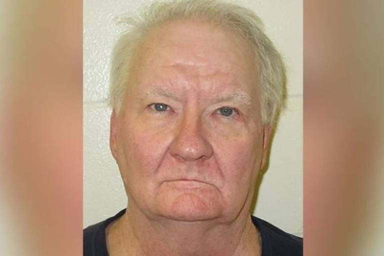 Foto de presidiário. Homem branco, calvo com cabelos brancos ralo, boca fina e olhos irritados.