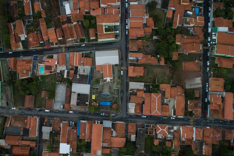 Foto aérea de uma cidade pequena; ruas cinzas dividem quarteirões com casas de telhado terracota