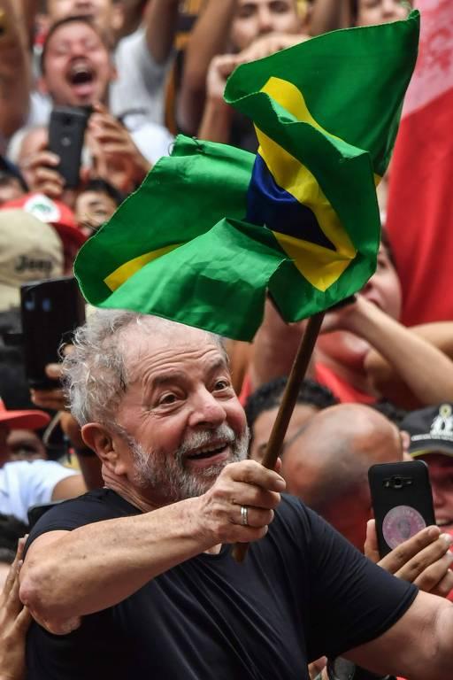 O ex-presidente Luiz Inácio Lula da Silva agita uma bandeira brasileira enquanto é carregado pela multidão de apoiadores em frente ao Sindicato dos Metalúrgicos em São Bernardo do Campo, região da grande São Paulo