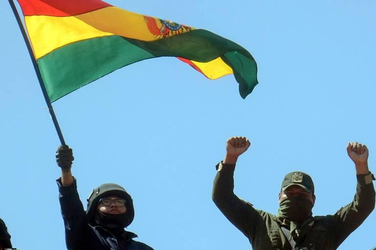 Homens vestidos de preto balançando bandeira vermelha, amarela e verde da Bolívia.