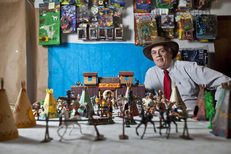Vários brinquedos sobre uma mesa e homem de chapeu de caubói ao fundo