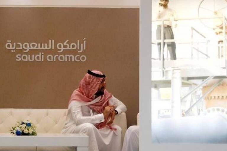 Homem com trajes típicos sauditas sentado diante de duto de petróleo