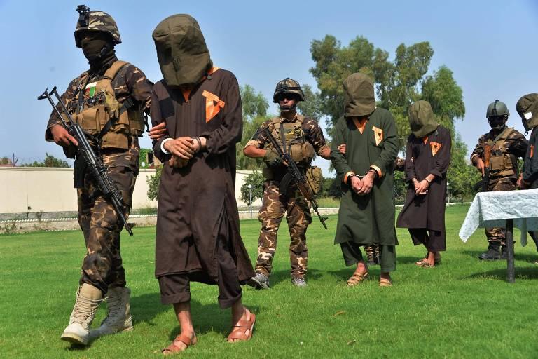 soldados escoltam presos