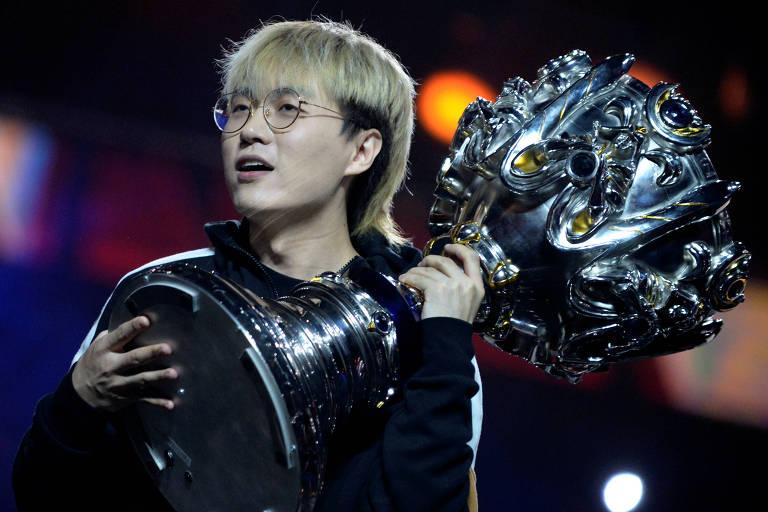 Chang 'Xinyi' Ping do time FunPlus Phoenix com troféu após vencer campeonato mundial de LoL (League of Legends)