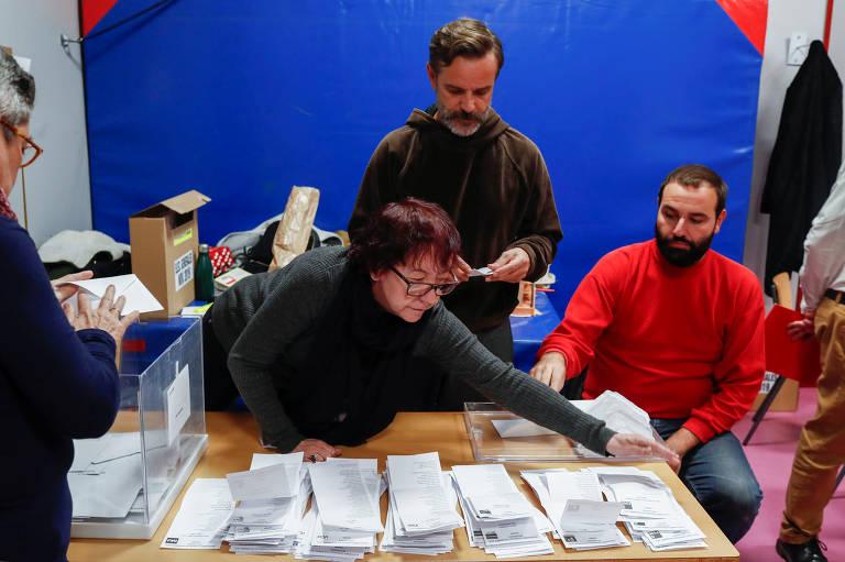 3 pessoas manuseiam centenas de papéis em cima de uma mesa