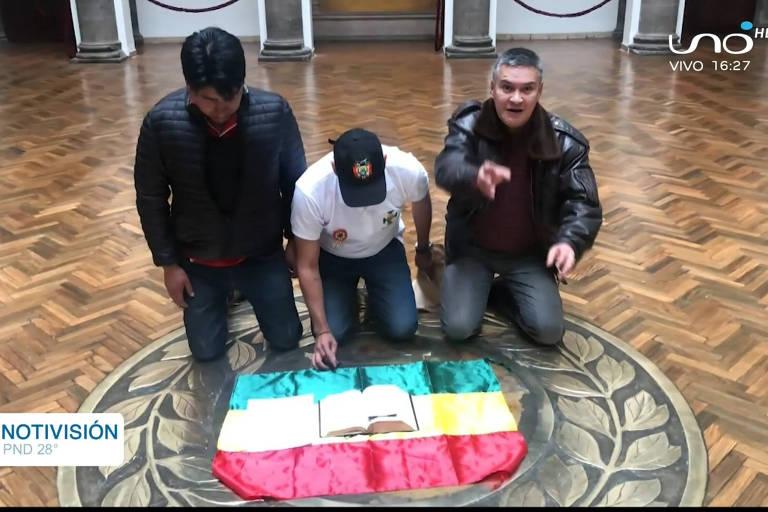 O líder opositor Luis Fernando Camacho (ao centro) ajoelhado diante de uma Bíblia e da bandeira da Bolívia, no Palácio Quemado, sede do governo, em La Paz; ele levou para o local uma carta de renúncia para ser assinada por Evo