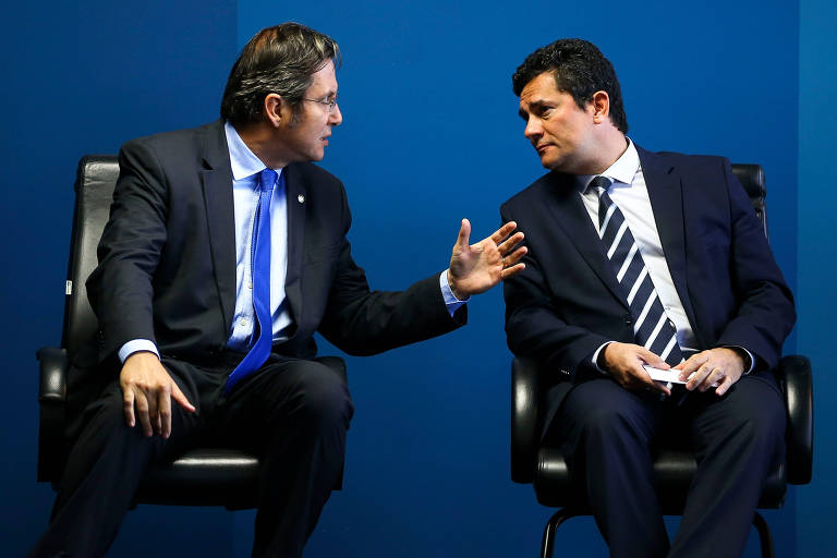 Os dois homens estão sentados lado a lado, em cadeiras altas, de terno e gravata. Fabiano Bordignon, à esquerda, está voltado para o ministro, à direita, gesticulando e falando, enquanto Moro o ouve