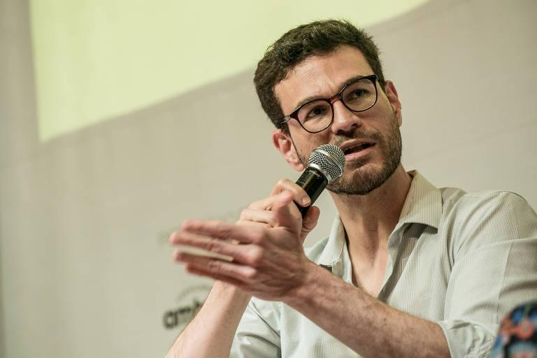 homem de óculos segura microfone em evento
