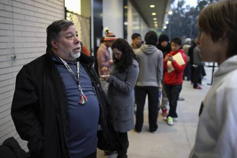 ORG XMIT: LOA005 REFILE - CORRECTING DATE  Apple co-founder Steve Wozniak (L) talks to a customer as he and his wife Janet (not pictured) wait in line overnight with customers to purchase the new iPad at the Apple Store in Century City Westfield Shopping Mall, Los Angeles, California March 16, 2012. The launch of Apple's 4G-ready tablet computer comes as the company's share price hit $600 for the first time. REUTERS/David McNew (UNITED STATES - Tags: BUSINESS SCIENCE TECHNOLOGY)
