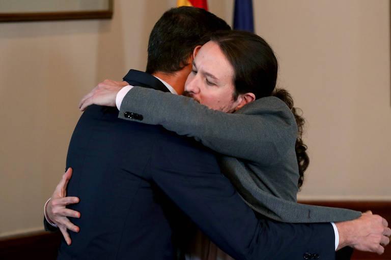 O premiê Pedro Sánchez e o líder do Podemos, Pablo Iglesias (de frente), se abraçam durante anúncio de acordo