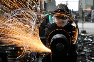 Worker polishes a bicycle steel rim at a factory manufacturing sports equipment in Hangzhou, Zhejiang