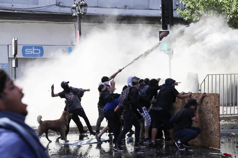 Manifestantes se protegem de jato de água lançado pelas forças de segurança durante protesto anti-governo em Santiago