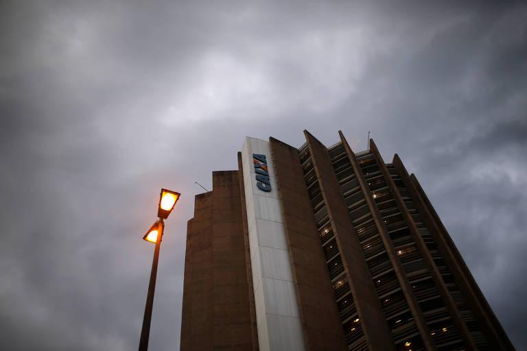 Sede da Caixa Econômica Federal em Brasília é vista de baixo, com um céu nublado em cor cinza escuro acima.