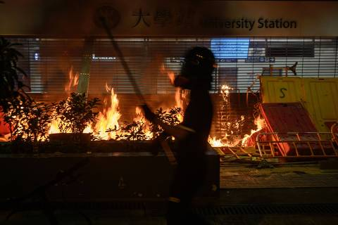 Protesters burn the entrance gate of a metro station after the clashes with protesters at the Chinese University of Hong Kong (CUHK), in Hong Kong on November 13, 2019. - Hong Kong pro-democracy protesters clashed with riot police in the city's upmarket business district and on university campuses on November 12, extending one of the most violent stretches of unrest seen in more than five months of political chaos. (Photo by Philip FONG / AFP)
