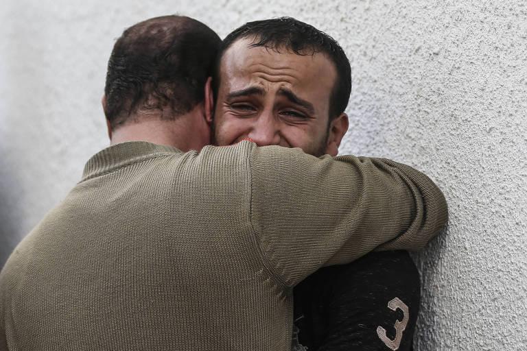 Homens se abraçam e choram encostados em uma parede