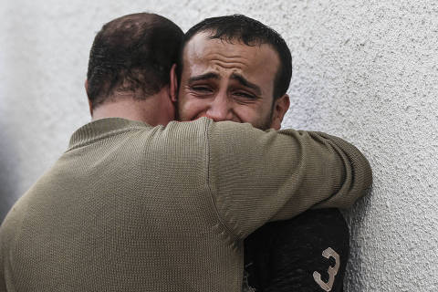 Palestinian men mourn outside the morgue of al-Shifa hospital in Gaza City on November 13, 2019. - Two more Palestinians were killed in an Israeli strike in the Gaza Strip, the enclave's health ministry said, as Israel said it was targeting rocket-launching squads and militant sites. The deaths brought the Gaza toll to 18 people killed since an exchange of fire began on Tuesday with an Israeli targeted strike on an Islamic Jihad commander sparking retaliatory rocket launches (Photo by MAHMUD HAMS / AFP) ORG XMIT: 121