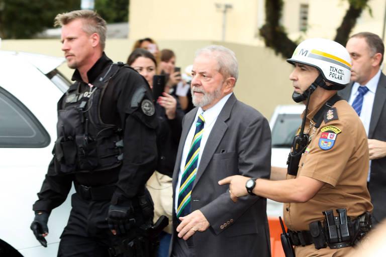 Lula é escoltado pelo policial federal Jorge Chastalo até o carro que o levaria para o prédio da Justiça Federal, em Curitiba