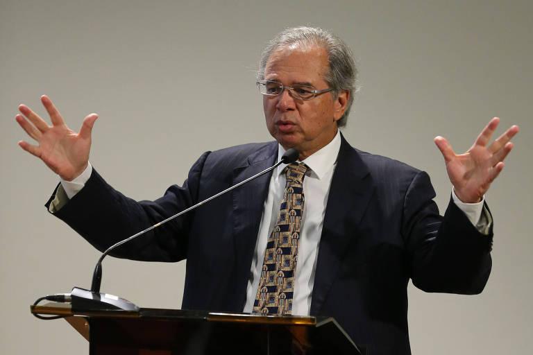 De terno preto e gravata estampada, Paulo Guedes discursa no microfone. Ele gesticula com as duas mãos, fazendo um movimento largo.