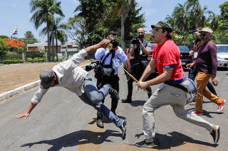 A supporter of Venezuela's President Nicolas Maduro fights with an opposition leader Juan Guaido's supporter outside Venezuelan embassy in Brasilia
