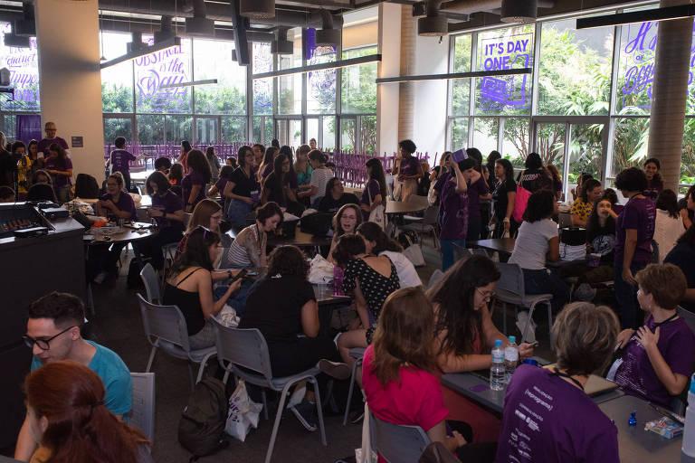 Espaço amplo com muitas cadeiras, mesas e notebooks; mulheres conversam entre si