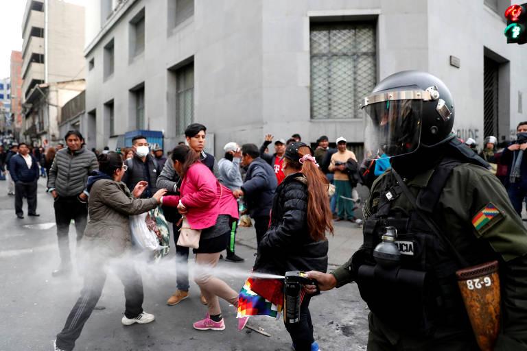 Policial, de capacete, dispara jato contra manifestantes