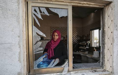 A Palestinian woman stands by the window of her house damaged in an Israeli air strike on November 14, 2019 in Khan Yunis in the southern Gaza Strip. - For the first time in more than a decade, Israeli forces have bombed Gaza without targeting Hamas. But this spells a tough choice for the Islamist movement, between heeding calls to join the fighting, and its desire to maintain its truce with Israel. Before dawn on November 12, Israeli forces struck an apartment in the northeastern Gaza Strip, killing Baha Abu al-Ata and his wife, who died immediately. (Photo by SAID KHATIB / AFP) ORG XMIT: 745