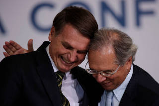 Brazil's President Jair Bolsonaro is greeted by Economy Minister Paulo Guedes during the ceremony of the 300 days of Government, in Brasilia