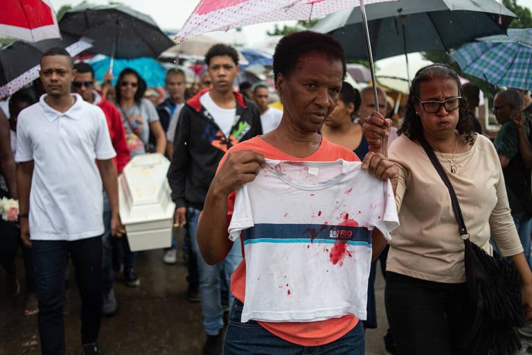 A tia-avó de Kethellen Umbelino de Oliveira Gomes, 5, segura camiseta durante enterro da menina no cemitério Murundu, em Realengo, zona oeste do Rio de Janeiro