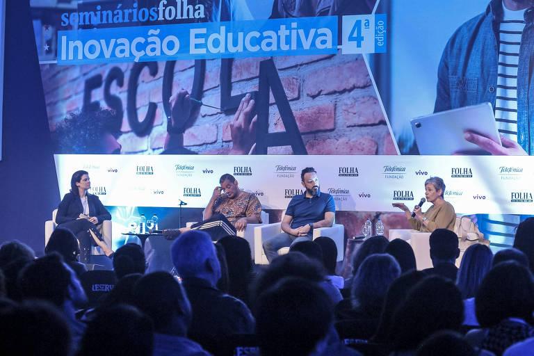Quatro pessoas sentadas em poltronas no palco de um auditório