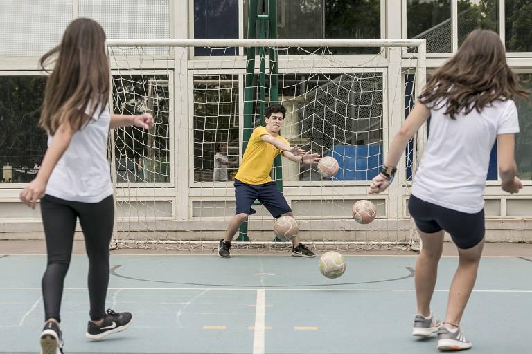 Duas meninas chutam para o gol, onde o goleiro é um menino