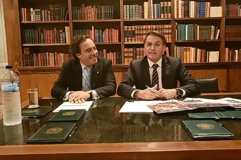 O presidente da Caixa, Pedro Guimarães, com Jair Bolsonaro em transmissão ao vivo em rede social nesta quinta-feira (14)