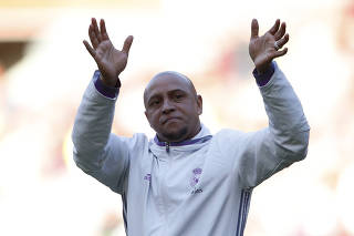 Real Madrid's Roberto Carlos applauds fans after the match